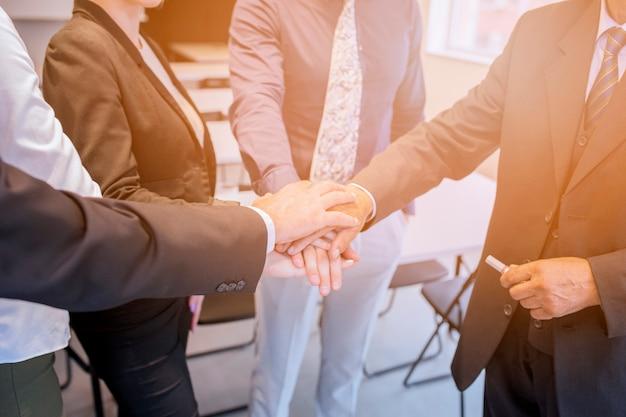 Equipo corporativo apilando la mano del otro en la oficina.