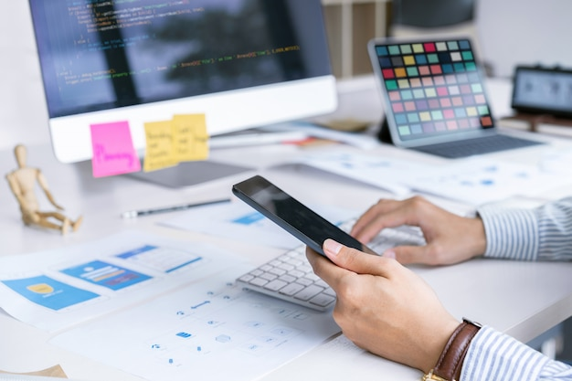 Equipo creativo de diseñadores de front-end de inicio que se concentra en la pantalla de la computadora para diseñar, codificar y programar aplicaciones móviles.