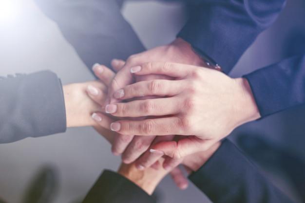 Equipo creativo juntando sus manos en círculo