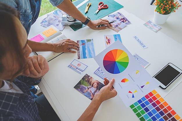 Equipo creativo del lanzamiento del diseñador asiático de la publicidad que discute ideas en oficina.