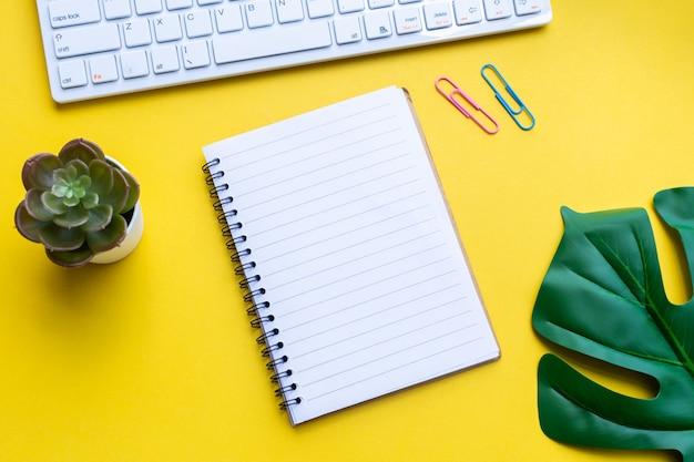 Equipo y cuaderno vacío con amarillo.