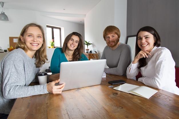 Equipo de cuatro personas exitosas posando en la sala de reuniones
