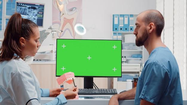 Equipo de cuidado bucal mirando la pantalla verde horizontal en el monitor