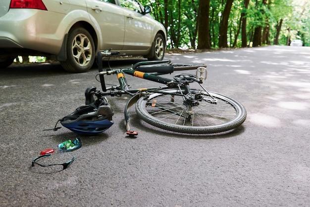 Equipo dañado. bicicleta y accidente de coche de color plateado en la carretera en el bosque durante el día