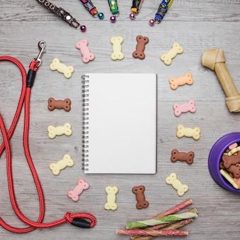 Equipo de cuidado de perros y aperitivos con notebook