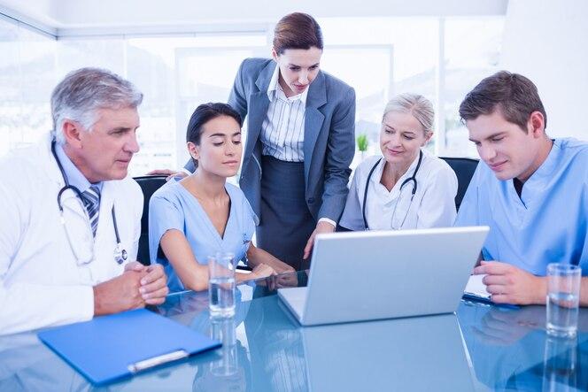 Equipo de médicos y empresaria tener una reunión en consultorio médico