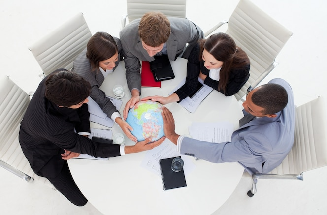 Equipo de negocios internacionales sosteniendo un globo terrestre