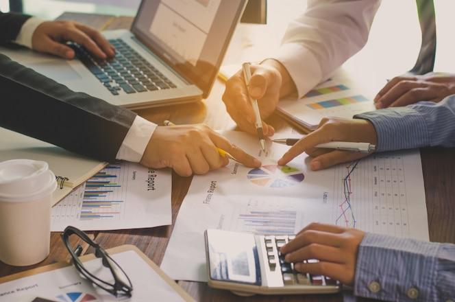 Equipo de negocios trabajando con la computadora portátil en la oficina de espacio abierto. informe de la reunión en progreso.