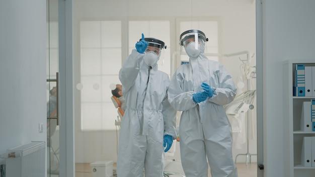 Equipo de dentistas caucásicos con trajes de materiales peligrosos discutiendo la prevención