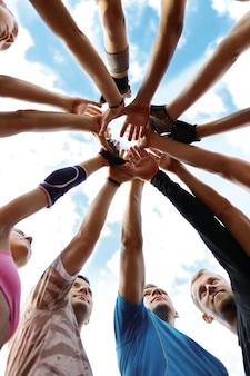 Equipo de deporte, manos arriba, alegre, sonriente, contento, ejercicio, juntos, estilo de vida, amigos, amor, relación, unidad, gente, ventilador, manos, ganadores Foto gratis