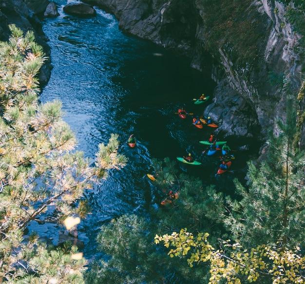 Equipo deportista de kayakistas que desciende en un kayak de río de montaña.