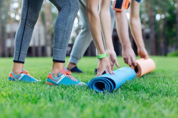 Equipo deportivo. cerca de esteras de yoga puestas en la hierba por deportistas sanos