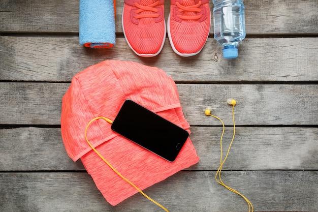 Equipo deportivo y teléfono inteligente con auriculares sobre fondo de madera.