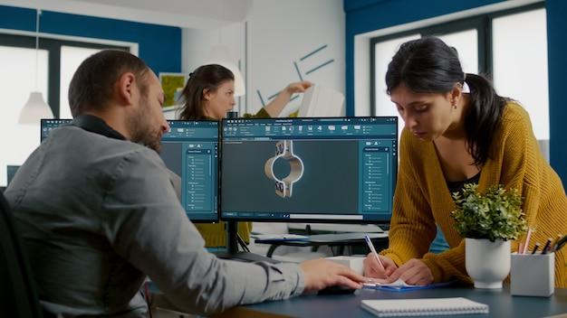 Equipo discutiendo sobre un proyecto industrial usando la configuración de monitores duales para diseñar engranajes y clavijas metálicas ...