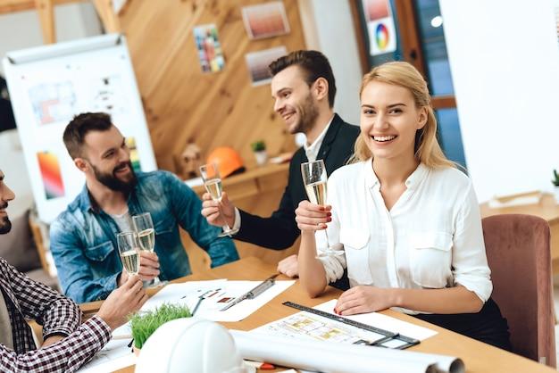 Equipo de diseñadores arquitectos bebiendo champán.