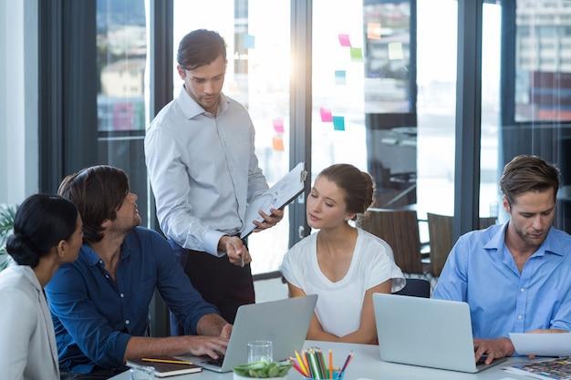 Equipo de diseñadores gráficos discutiendo sobre laptop