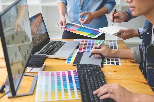 Equipo de diseñadores gráficos que trabajan en diseño web con muestras de color que editan ilustraciones usando una tableta y un lápiz óptico en el escritorio de escritorios en la oficina creativa.