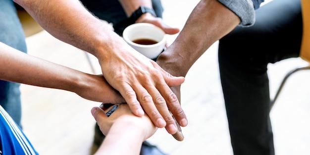 Equipo diverso apilando las manos en el medio