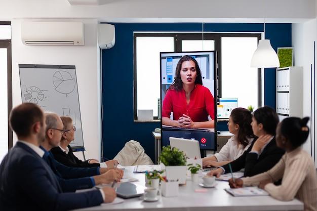 Equipo diverso de compañeros de trabajo hablando con el gerente de proyecto mediante cámara web