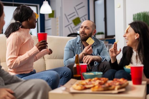 Equipo diverso de compañeros de trabajo jugando charadas después del trabajo