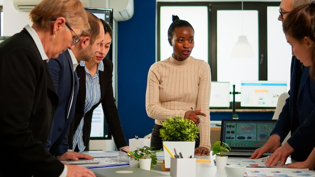 Equipo diverso de compañeros de trabajo profesionales, intercambiando ideas en una reunión de negocios bajo la atenta mirada de la jefa africana. compañía de director negro evaluando a los empleados sentados en el escritorio discutiendo