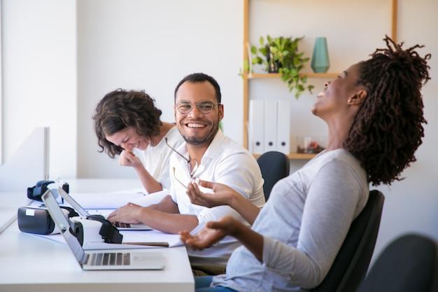 Equipo diverso de desarrolladores de realidad virtual conversando mientras prueba el producto