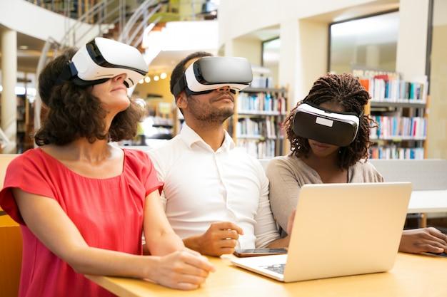 Equipo diverso de estudiantes adultos que usan tecnología vr para el trabajo.