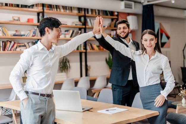Equipo diverso de hombres de negocios dando cinco altos el uno al otro