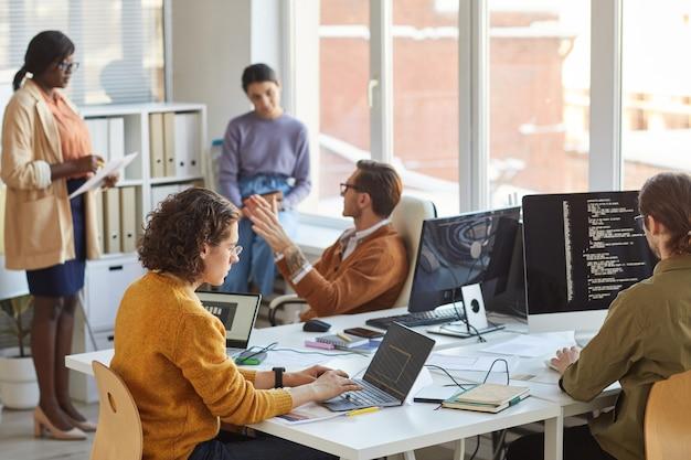 Equipo diverso de programadores de software jóvenes que usan computadoras y escriben código mientras colaboran en un proyecto en el estudio de desarrollo de ti, espacio de copia