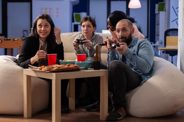 Equipo diverso de trabajadores jugando juegos de consola en la televisión en la oficina después del trabajo usando joysticks