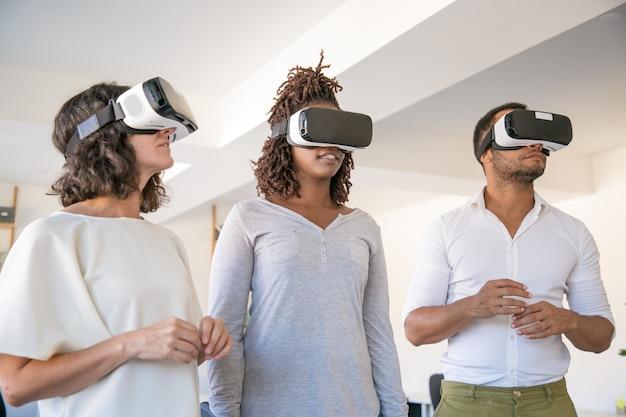 Equipo diverso de tres personas que disfrutan de la experiencia de realidad virtual