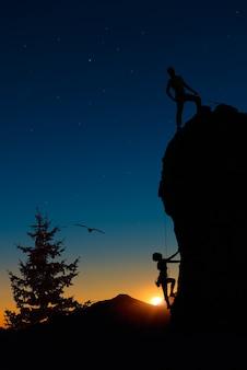 Equipo de dos montañeros con cuerdas escalan la montaña