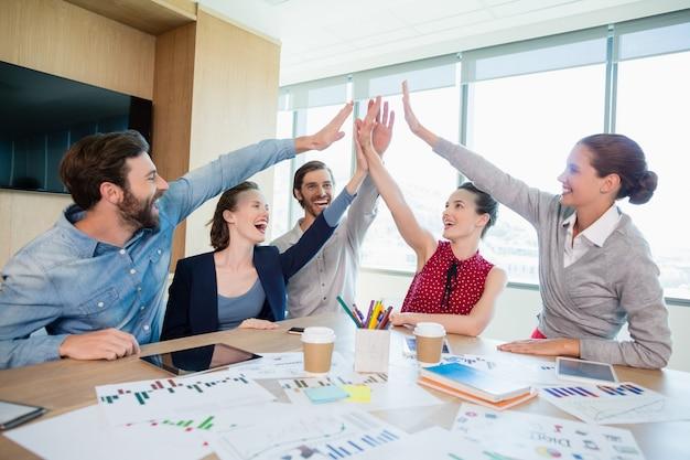 Equipo de ejecutivos de negocios dando cinco en la sala de conferencias