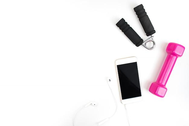 Equipo de ejercicio con pesas de color rosa, teléfonos inteligentes, auriculares en un fondo blanco.