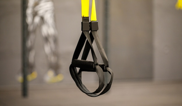 Un equipo de ejercicios llamado trx que estaba preparado para jugar al mediodía en un gimnasio.