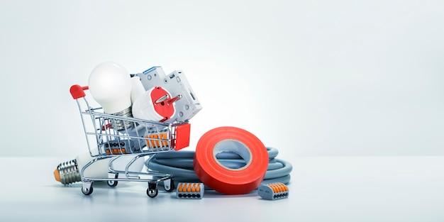 Equipo de electricista en un carrito de compras y en el piso sobre fondo blanco.