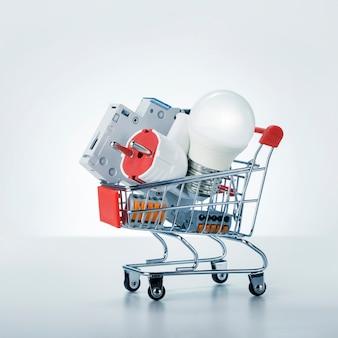 Equipo de electricista en un carrito de compras sobre fondo blanco.