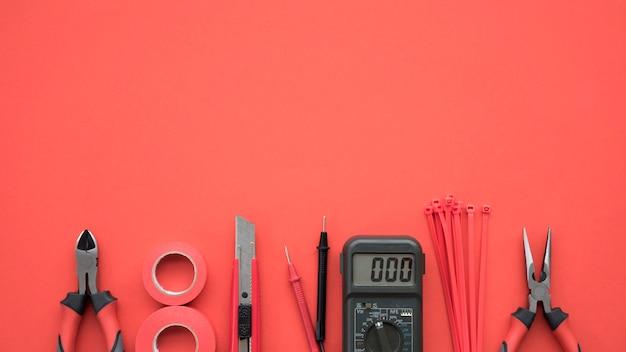 Equipo eléctrico dispuesto en el fondo de fondo rojo.