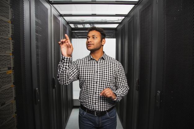 Equipo electronico. técnico de ti pensativo de pie en la sala de servidores y apuntando con el dedo