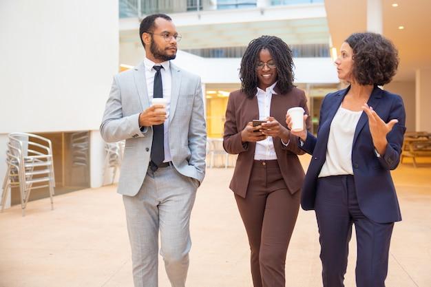 Equipo emocionado discutiendo proyecto mientras bebe café