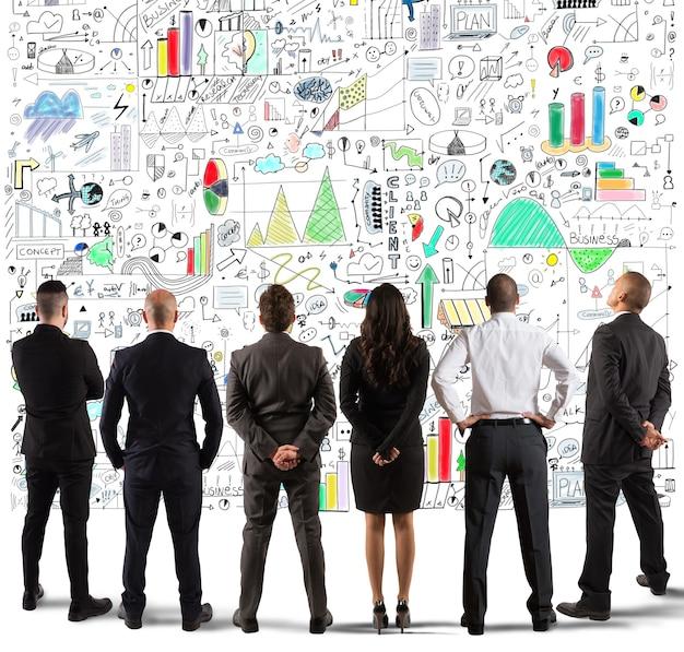 Equipo empresarial dibujando un nuevo proyecto complejo en la pared