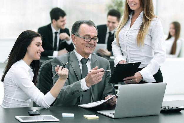 Equipo empresarial discutiendo con el jefe de datos financieros.