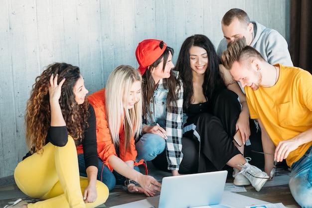 Equipo empresarial milenario trabajando juntos. diverso grupo de jóvenes sentados en el suelo.