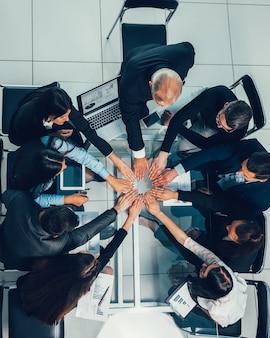 Equipo empresarial mostrando su unidad en el lugar de trabajo