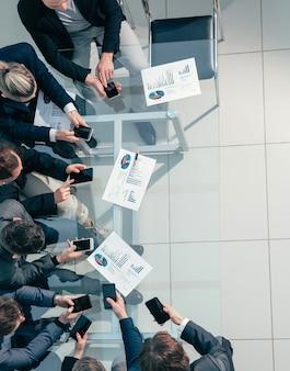 El equipo empresarial usa sus teléfonos inteligentes para trabajar con datos financieros
