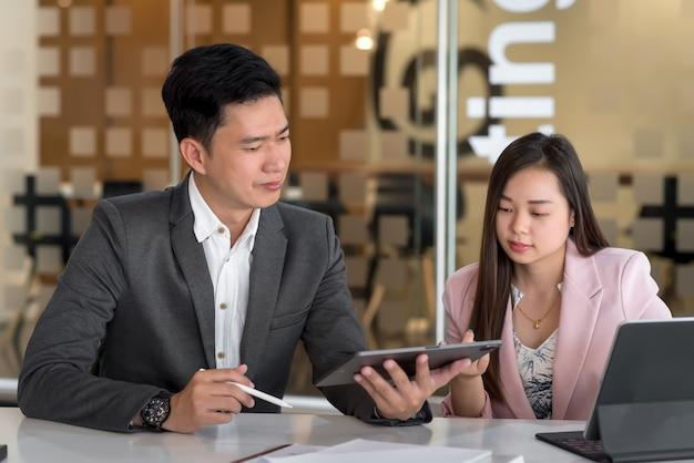 Equipo de empresario y empresaria trabajan juntos analizan su trabajo en la oficina.