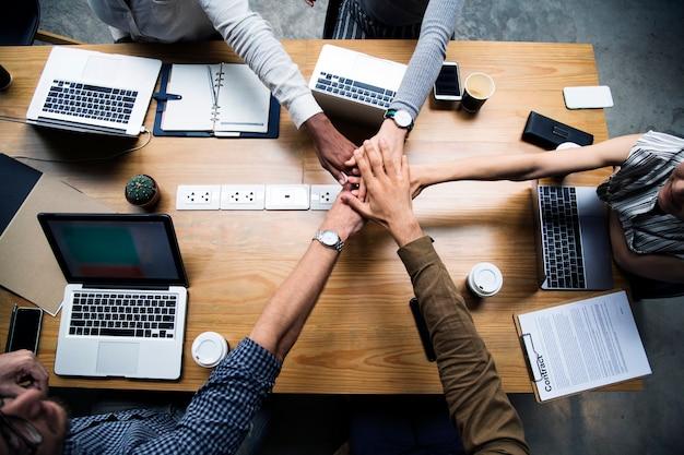 Equipo de empresarios apilando las manos