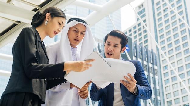 Equipo de empresarios asiáticos, hombres y mujeres inteligentes, hablan y presentan el proyecto con un archivo de papel en un paseo peatonal al aire libre en el edificio moderno del espacio de la ciudad