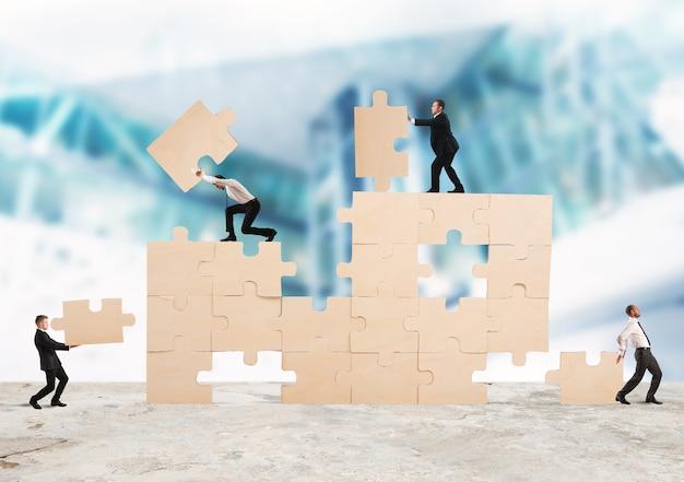 Equipo de empresarios colaboran y cooperan para construir un rompecabezas.