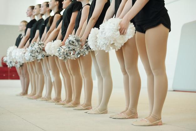 Equipo escolar de porristas sosteniendo pompones y de pie en fila